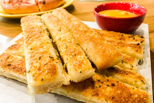 99¢ Breadsticks & Sauce with Purchase of Any Pizza at Holiday Pizza & Chuck's Catering
